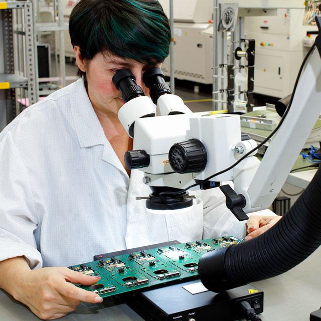 Wirtschaftsschwerpunkte, Neue Materialien – Frau schaut sich Technik unter dem Mikroskop an