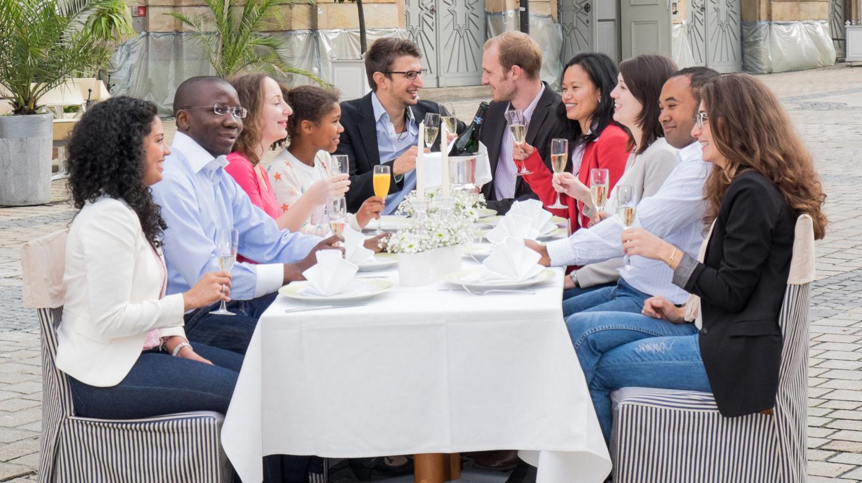 Personen sitzen an einem gedeckten Tisch
