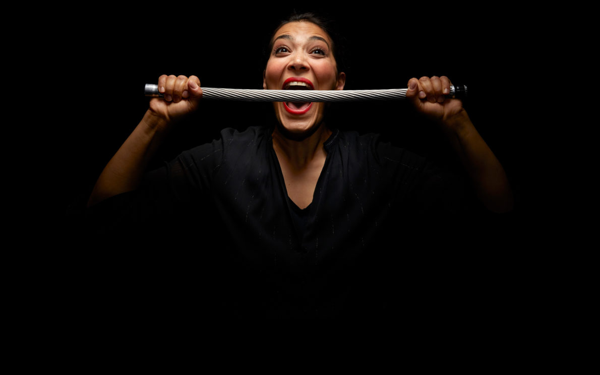 Frau beißt auf Stahlseil