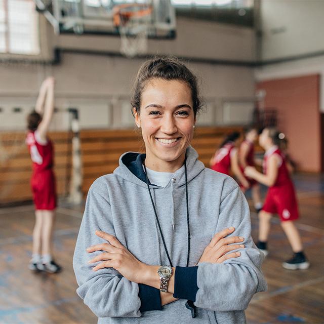 Frau als Sport-Vereinsleiterin und im Hintergrund spielen Personen Basketball