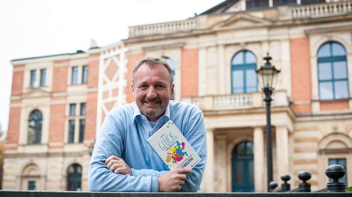 """Stephan Müller mit seinem neuen Buch """"Unsere Glücksmomente"""" vor dem Festspielhaus, wo einige Geschichten spielen. Foto: Eric Waha"""