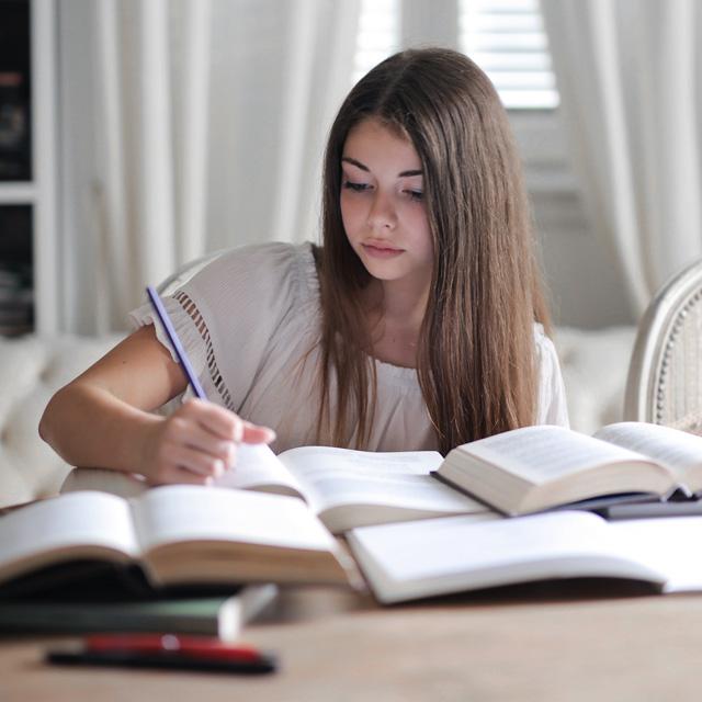 Sprache lernen – Mädchen sitzt vor Büchern