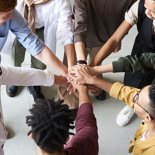 Personen legen Hände in der Mitte zusammen