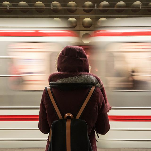 Frau steht vor fahrendem Zug