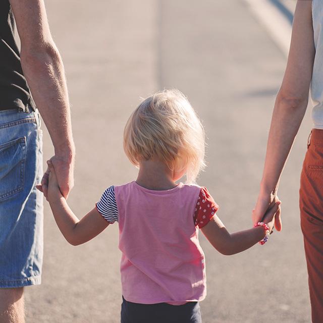 Mutter und Vater halten Hand mit Kind