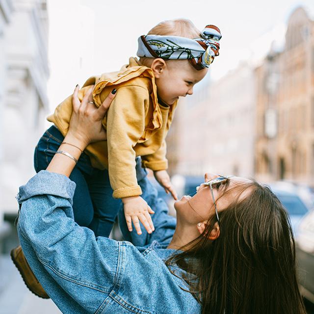 Mutter hält Kind in den Armen und lacht