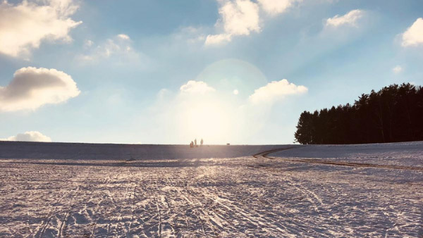Personen in der Ferne eines verschneiten Feldes