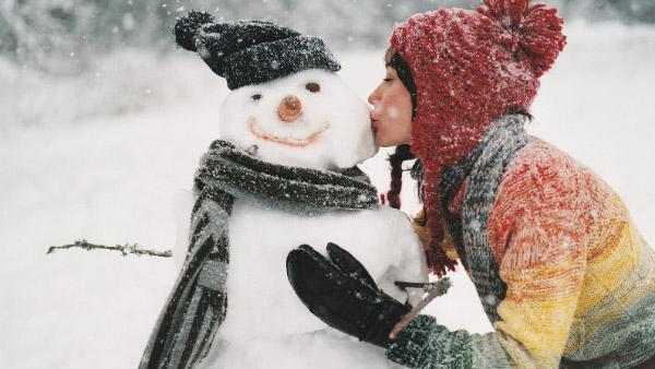 Frau küsst Schneemann