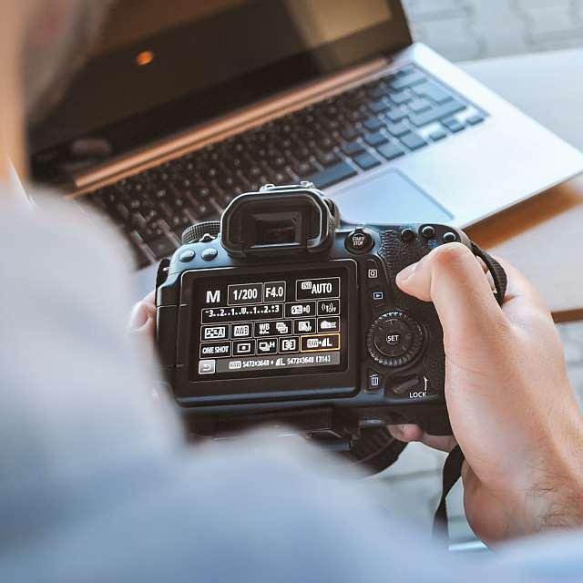 Person hält einen Fotoapparat in der Hand